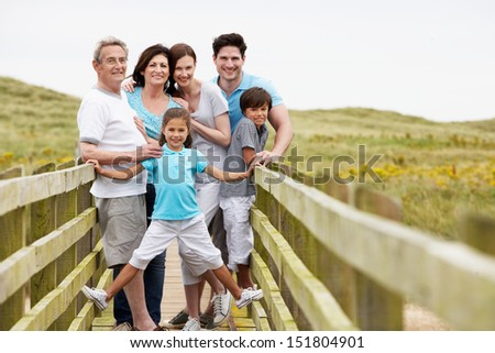 Multi Generation Family Walking Along Wooden Bridge - stock photo