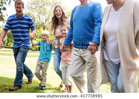 Multi-generation family walking together in the park on a sunny day - stock photo