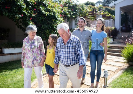 Multi-generation family walking together on the garden path - stock photo