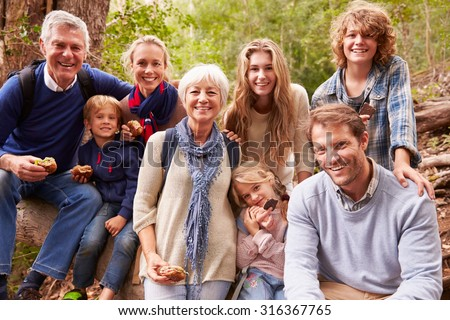 Multi-generation family with teens eating outdoors together - stock photo