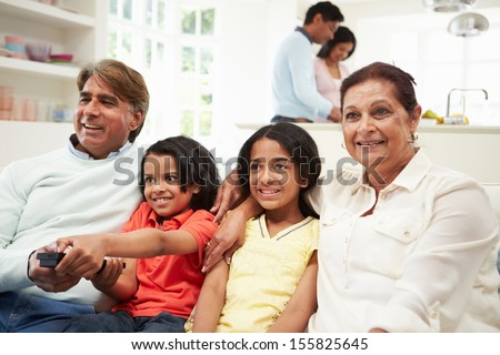Multi-Generation Indian Family Sitting On Sofa Watching TV - stock photo