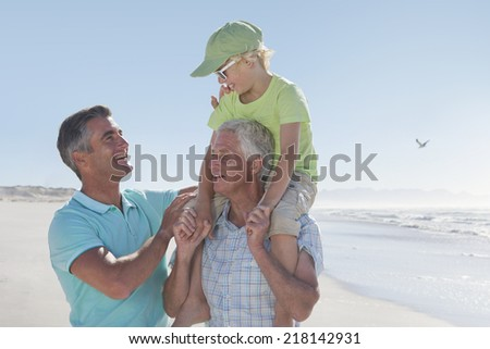 Multi-generation men on sunny beach - stock photo