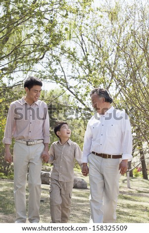 Multi-generational family holding hands and walking - stock photo
