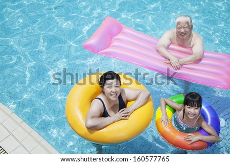 Multi-generational family playing in pool with inflatable tubes - stock photo