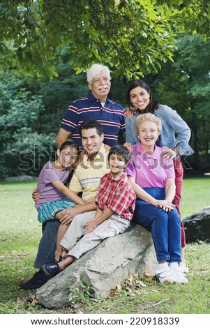 Multi-generational Hispanic family smiling in park - stock photo
