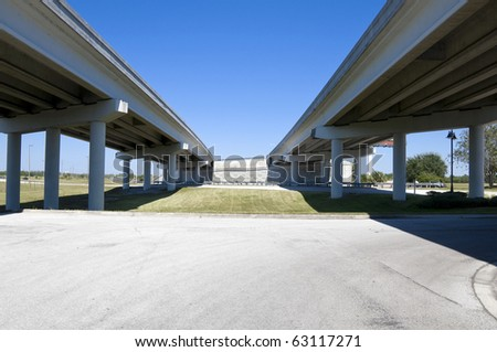 Multi-lane expressway overpass showing structural columns with blue sky