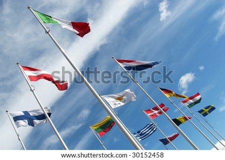 Multi national flags flutter in blue cloudy sky