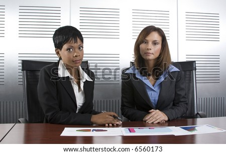 Multi-racial business team working within an office with a sales graphs - stock photo