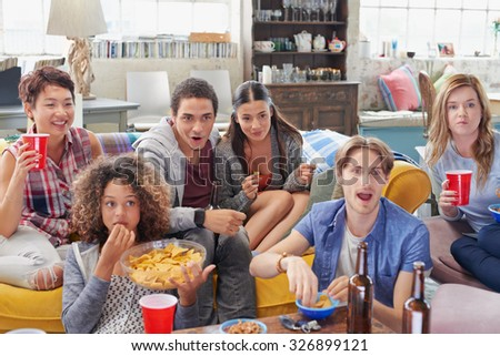 Multi racial group of  student friends sports fans excited drinking beer eating chips watching football on TV