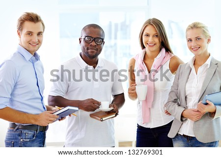 Multi-racial team of four being ready to collaborate - stock photo