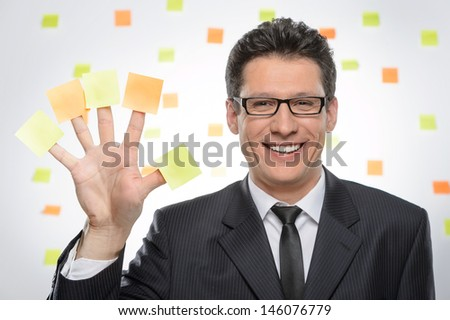 Multi-tasking businessman. Portrait of cheerful businessman showing his hand with sticky notes on each finger - stock photo