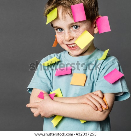 multi-tasking preschool activity - cute 6-year old boy with freckles smiling with copy space sticky notes all over the body to remember all his ideas, indoors  - stock photo