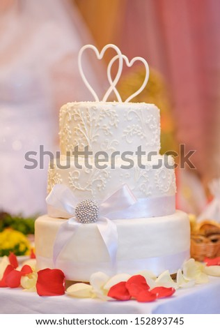 Multi-tiered white wedding cake with two hearts above - stock photo