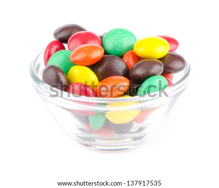 Multicolor candies in glass bowl, isolated on white - stock photo
