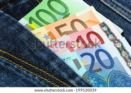 Multicolor Euro banknotes in blue jeans pocket - stock photo