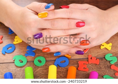 Multicolor female manicure with markers on wooden background