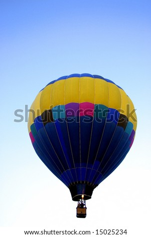 Multicolor hot air balloon against blue graduated sky with room for text - stock photo