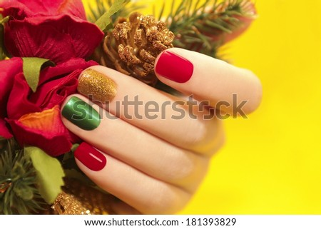Multicolor manicure with red,green and yellow brilliant varnish for the nails on a yellow background with rose and Christmas tree. - stock photo