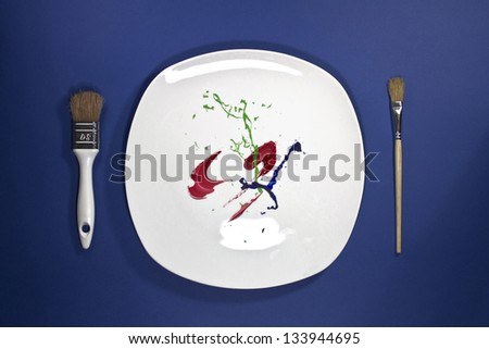 Multicolor paint on the plate with paint brushes on side - stock photo