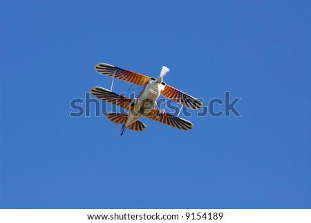 Multicolor painted aerobatic biplane against bright blue sky - stock photo