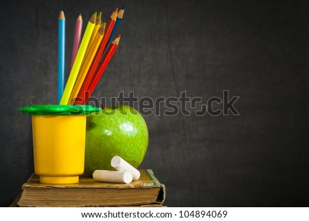 Multicolor pencils, chalks and green apple on old book against blackboard with copy space. School concept - stock photo