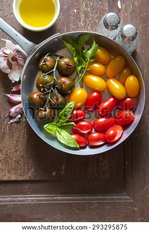 multicolor red and yellow cherry Grape Tomatoes in an aluminum pan for cooking breakfast or healthy summer lunch - stock photo
