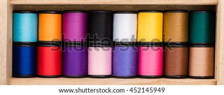 Multicolor sewing threads background. Wooden background - stock photo