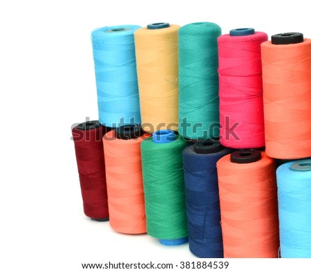 Multicolor sewing threads on background. focus on the blue thread - stock photo