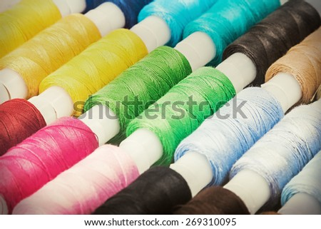 Multicolor sewing threads on wooden background. focus on the green thread. Toning image - stock photo