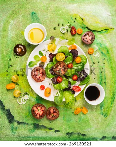 Multicolor Tomatoes salad with dressing oil and vinegar on green background, top view - stock photo