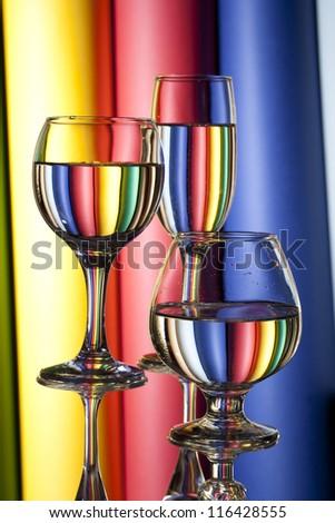Multicolor wine glasses against vertical multicolor strips - stock photo
