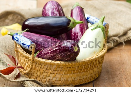 Multicolored aubergines in a basket  - stock photo