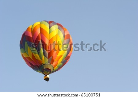 Multicolored balloon against blue sky - stock photo