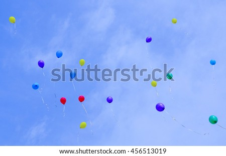 Multicolored balloons flying high in the blue sky - stock photo