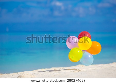 Multicolored balloons on white tropical beach - stock photo