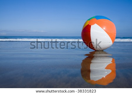 Multicolored beachball on the beach with reflection - stock photo