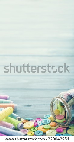 Multicolored buttons and spools of thread on light blue background - sewing concept - stock photo