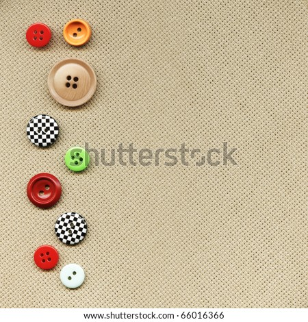 Multicolored buttons on the background fabric - stock photo