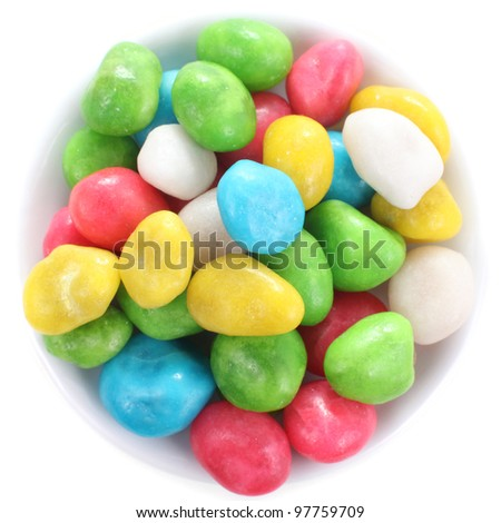 Multicolored candies on a little-little plate close up, isolated over white - stock photo
