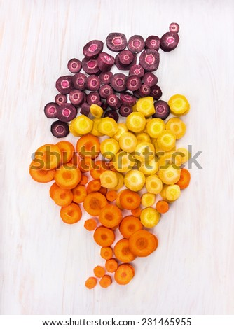 multicolored chopped carrots on white wooden table - stock photo