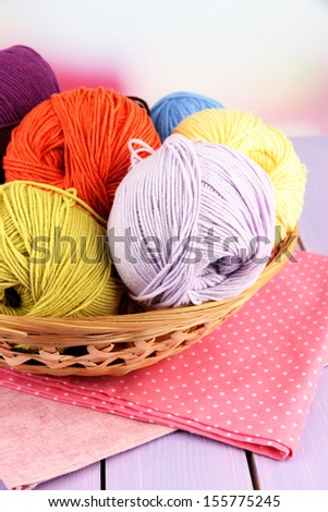 Multicolored clews in wicker basket with napkins closeup - stock photo