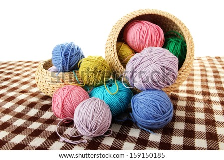 Multicolored clews in wicker basket with plaid closeup - stock photo