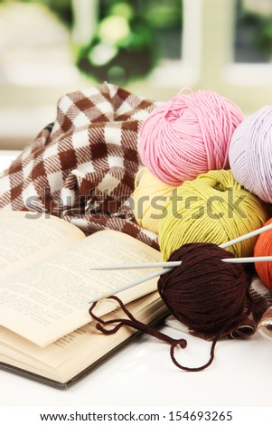 Multicolored clews with book and plaid closeup - stock photo