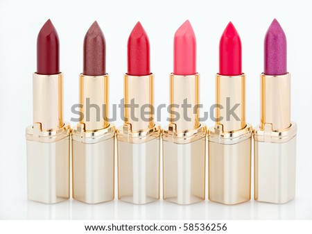 Multicolored color lipsticks arranged in line isolated on white - stock photo