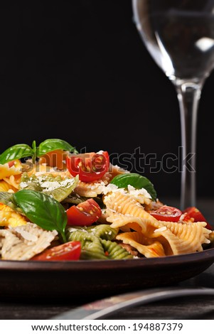 Multicolored cooked pasta meal on dark background