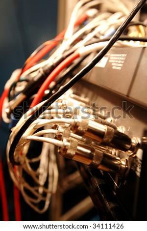 Multicolored cords of audio mixing desk in a sound-recording studio, blur, shallow depth - stock photo