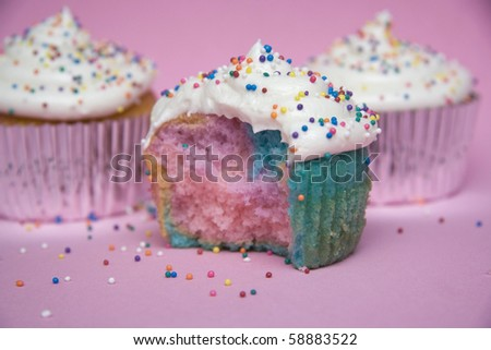Multicolored cupcakes with sprinkles on a pink background. - stock photo