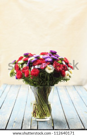 Multicolored daisy flower bouquet on a wooden table. (shallow focus)