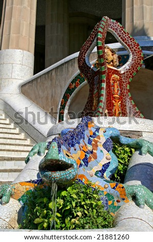 Multicolored dragon with ornamental brown tripod at Guell park, Barcelona, Spain - stock photo
