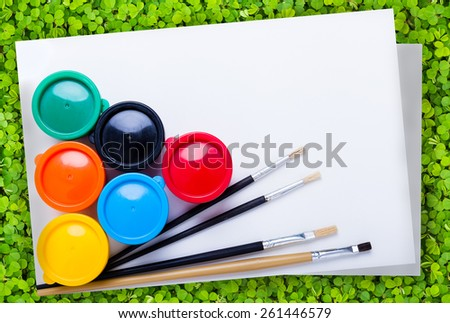 Multicolored drawing instruments (watercolor paints, paintbrush, blank sheet of paper) for create imagination over green clover background, creativity concept. Top view - stock photo